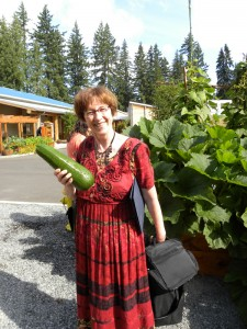 Carolyn Petersen holding a zucchini from the Hibulb Cultural Center