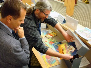 WSL Special Collections Librarian Sean Lanksbury, shows a new collection of Washington fruit box labels to Assistant Secretary of State, Ken Raske.